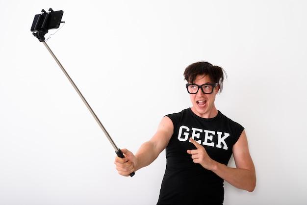 Człowiek nerd robi zdjęcie z telefonu komórkowego do selfie stick