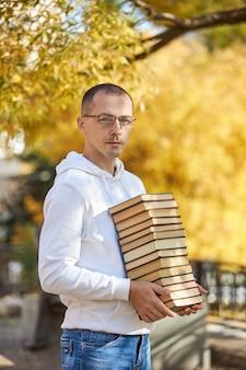 Człowiek niesie w rękach dużo książek. stos podręczników do szkolenia. przygotowanie do egzaminu