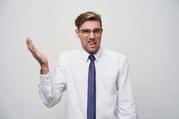 Człowiek niezadowolony ubrany w białą koszulę i niebieski krawat, z białymi okularami.