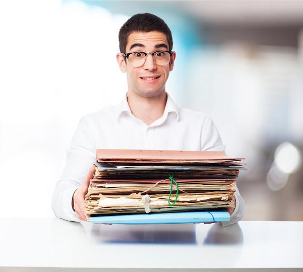 Człowiek niosący kilka folderów w biurze