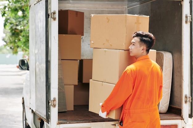 Człowiek niosący stos kartonów