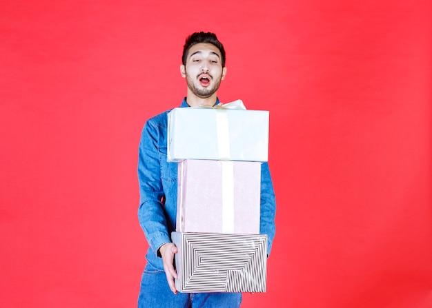 Człowiek niosący zapas ciężkich srebrnych pudełek prezentowych na czerwonej ścianie.