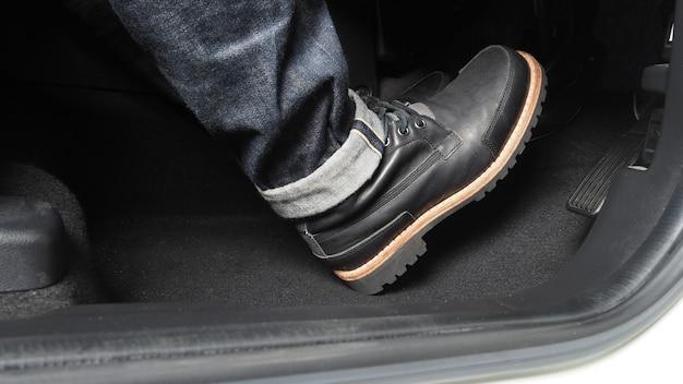 Człowiek noga i pedał przyspieszenia i hamulca wewnątrz samochodu lub pojazdu i kopiuje przestrzeń w kolorze czarnym;