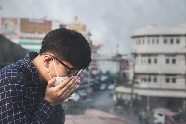 Człowiek nosi maskę z powodu zanieczyszczenia powietrza w mieście