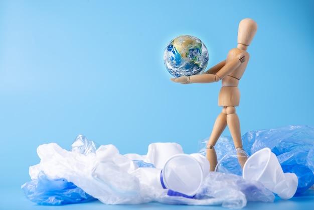 Człowiek nosi planetę w rękach, aby uratować ziemię przed śmieciami i plastikiem. elementy dostarczone przez nasa