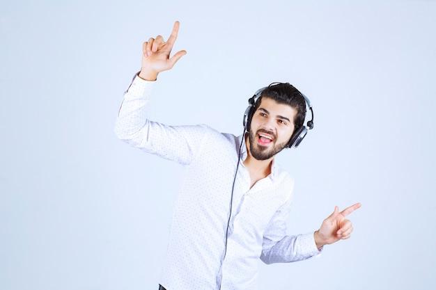Człowiek nosi słuchawki i słucha muzyki.