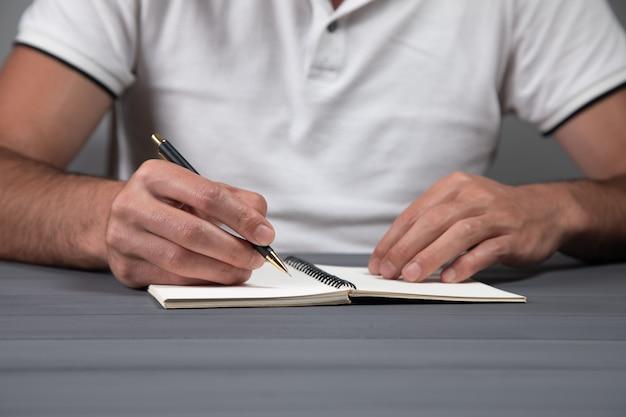 Człowiek notatek w notatniku na szarej ścianie