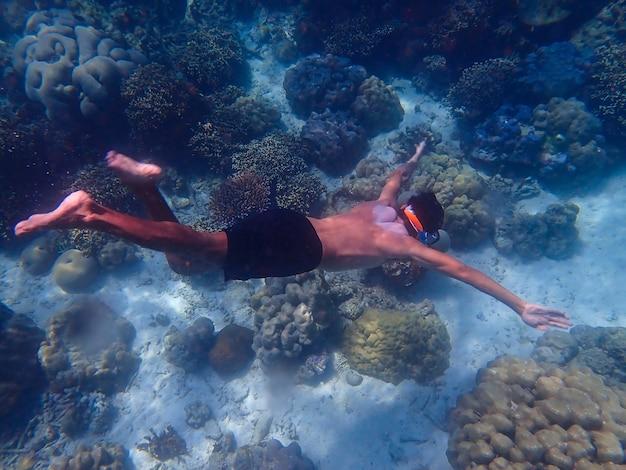 Człowiek nurkujący swobodnie pod wodą z widokiem na korale.