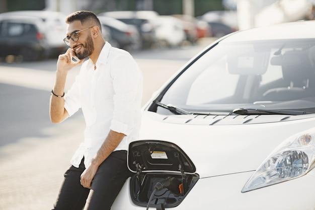 Człowiek o rozmowy przez telefon, czekając na samochód elektryczny. stacja ładowania, samochody ekologiczne. pochodzenie arabskie.