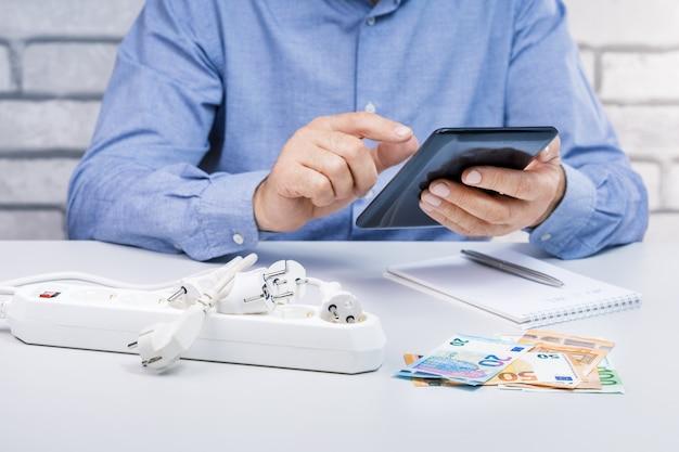 Człowiek oblicza energooszczędny dom lub zużycie energii elektrycznej. koncepcja oszczędzania energii z euro pieniędzy, wtyczek elektrycznych i człowieka z komputera typu tablet.
