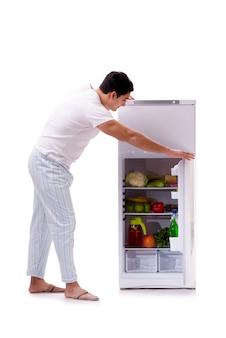 Człowiek obok lodówki pełnej jedzenia