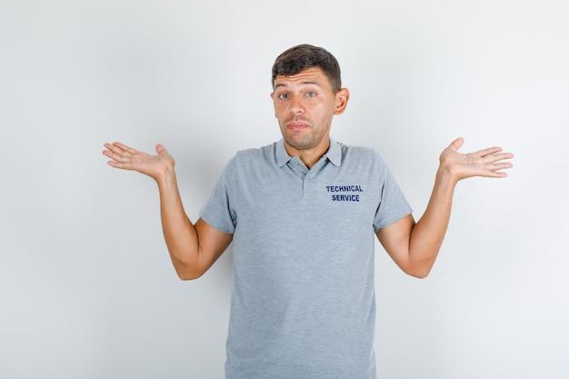 Człowiek obsługi technicznej pokazujący bezradny gest w szarym t-shircie i wyglądający na zdezorientowanego