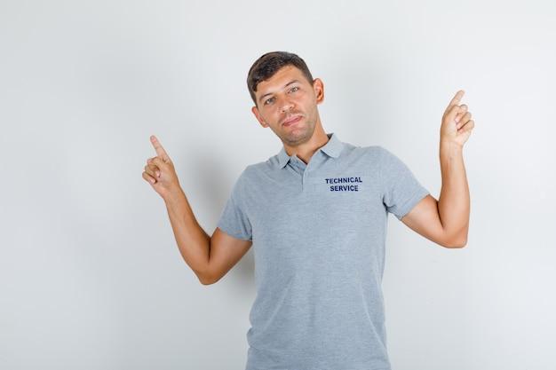 Człowiek obsługi technicznej pozuje, wskazując palcami w szarym t-shircie i patrząc wesoło