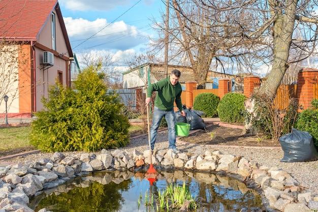 Człowiek oczyszcza staw ogrodowy z roślin wodnych i opadających liści