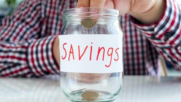 Człowiek oddanie monety w szklanym słoju z oszczędnościami. pojęcie finansów, wzrostu gospodarczego i oszczędności bankowych.