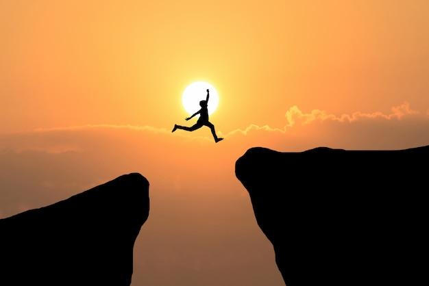 Człowiek odwagi przeskakiwać przez szczelinę między wzgórzem, koncepcją biznesową