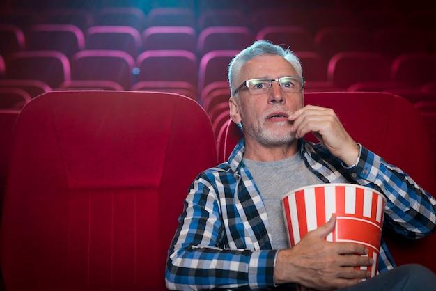 Człowiek ogląda film w kinie