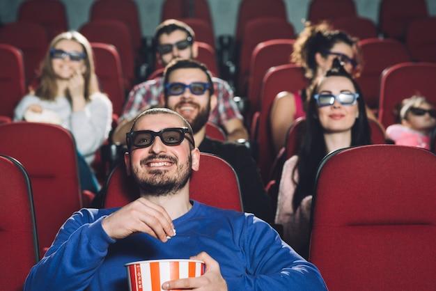 Człowiek ogląda film w pełnym kinie