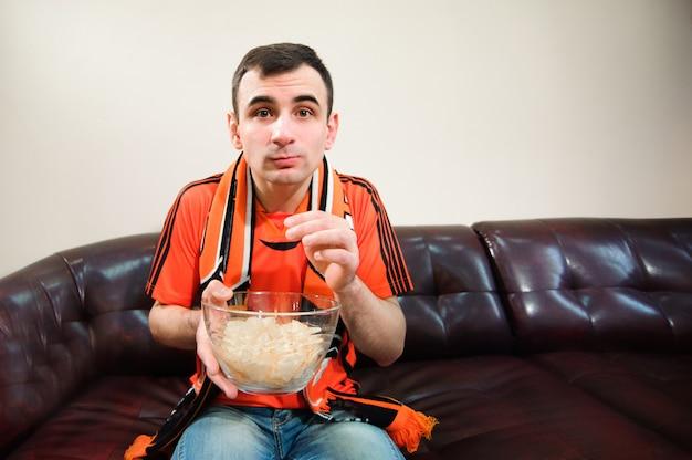 Człowiek ogląda piłkę nożną, kibica, sport w domu.