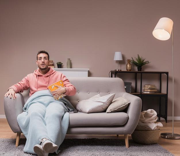 Człowiek ogląda telewizję z popcornem