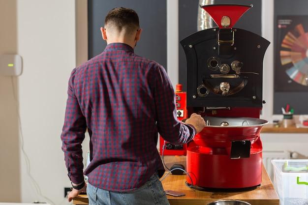 Człowiek oglądając aromatyczne ziarna kawy w nowoczesnym sprzęcie z chłodziarką do ziarna. koncepcja przemysłu. nowoczesna maszyna służąca do prażenia fasoli. palarni kawy wlewanej do cylindra chłodzącego.