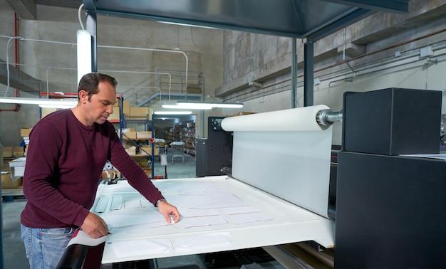 Człowiek operatora produkcji maszyny do transferu kalendarza