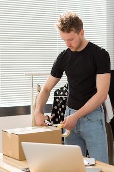 Człowiek pakuje pudełko w pomieszczeniu