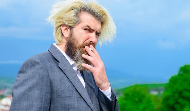 Człowiek palenia. stylowy brodaty mężczyzna z papierosem. biznesmen w garniturze dym papierosowy.