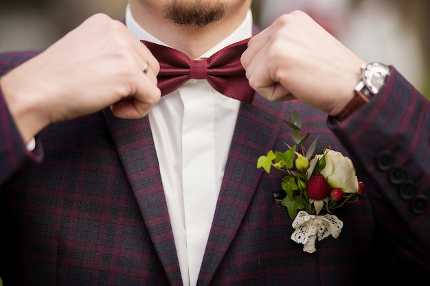 Człowiek pana młodego w stroju ślubnym z motylem