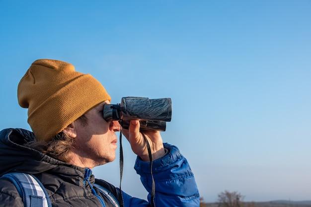 Człowiek patrząc przez zbliżenie lornetki