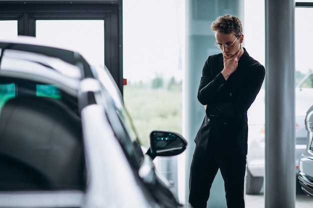 Człowiek patrzy na samochód i myśli o zakupie