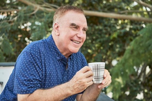 Człowiek pije kawę na zewnątrz