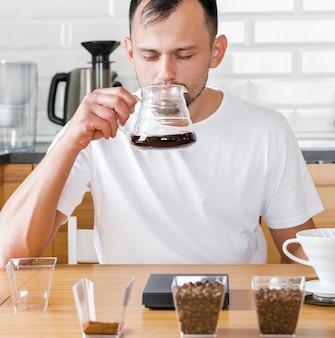 Człowiek pije kawę w pomieszczeniu