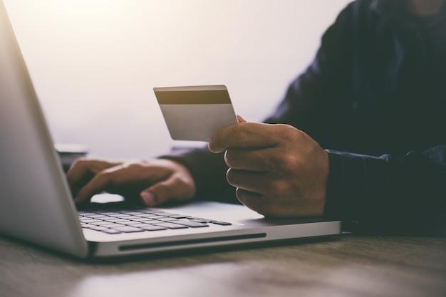 Człowiek pisania na laptopa do zakupów online i płacić kartą kredytową