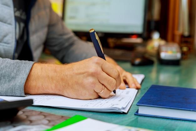 Człowiek pisania na papierze za pomocą pióra na stole.