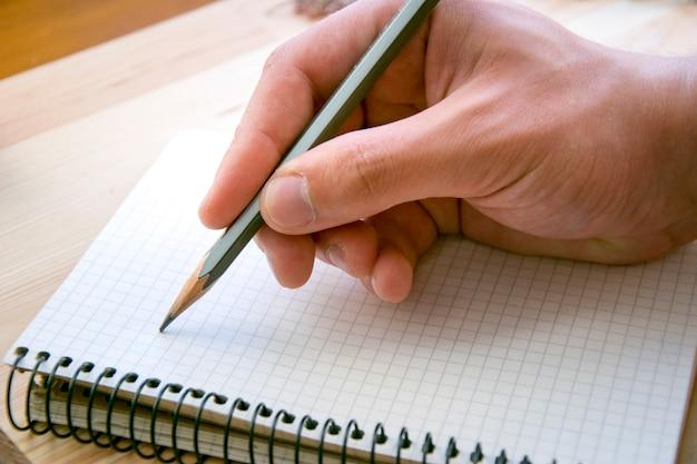 Człowiek pisze coś w osobistym papierowym notatniku