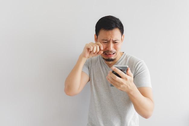 Człowiek płacze i smutny z tym, co pokazuje na smartfonie.