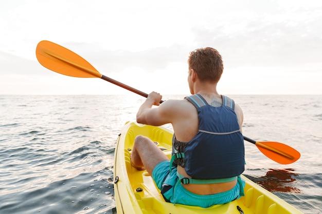 Człowiek, pływanie kajakiem po morzu jeziora w łodzi.