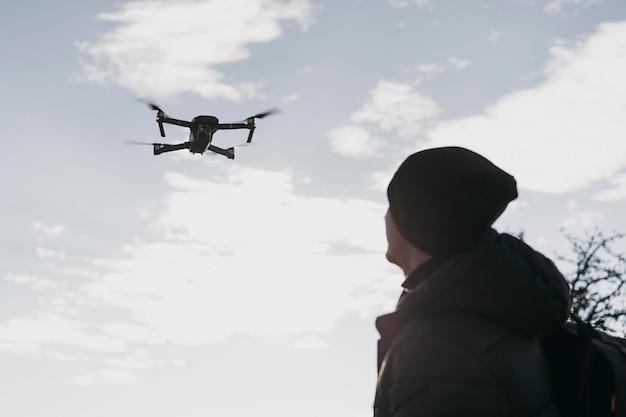 Człowiek pod niskim kątem oglądający drona