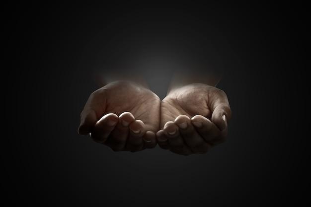 Człowiek podniósł ręce, modląc się do boga na czarnym tle