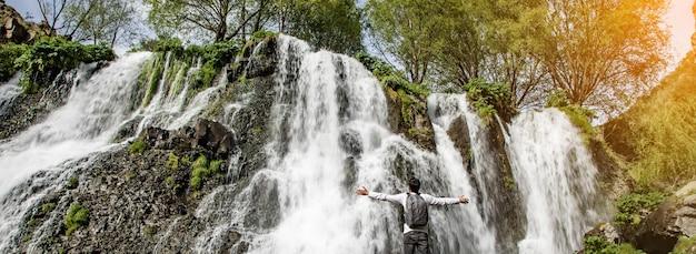 Człowiek podróżnik przed wodospadami.