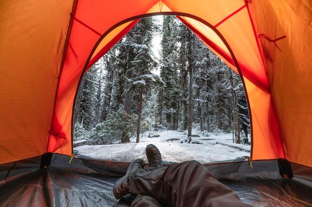Człowiek podróżnik relaks wewnątrz namiotu w lesie sosnowym na zimę w parku narodowym yoho, kanada