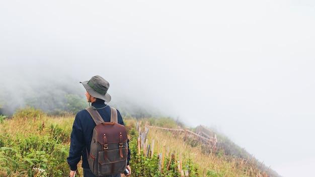 Człowiek podróżnik stojący na szczycie góry z białą chmurą mgły w przyrodzie