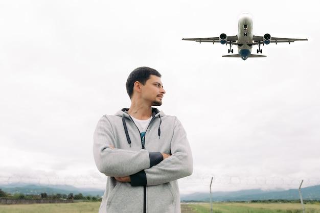 Człowiek podróżnik wstaje i patrzy, jak samolot startuje