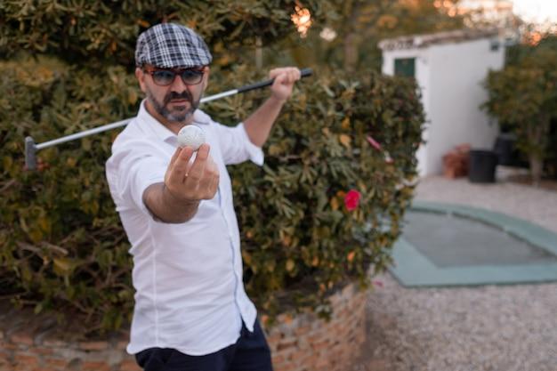 Człowiek pokazując piłeczkę golfową w dłoniach z kijem golfowym na plecach