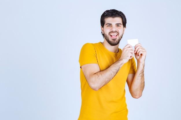 Człowiek pokazując swoją wizytówkę i prezentując się z ufnością.