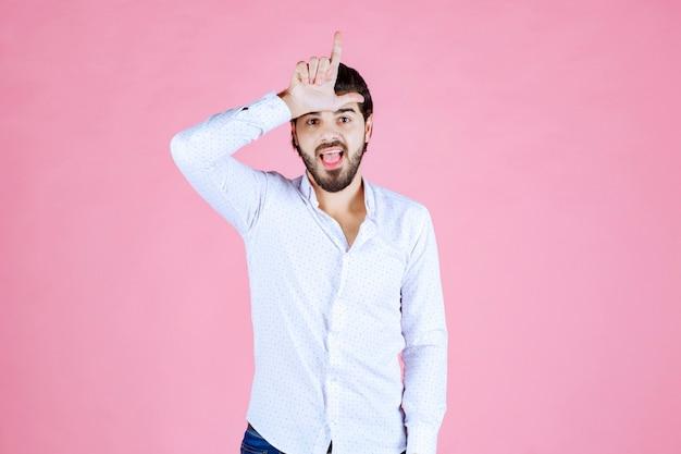 Człowiek pokazując znak ręką przegrany na czole.