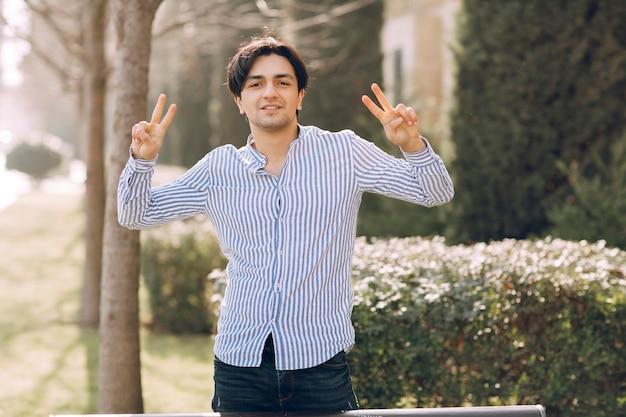 Człowiek pokazuje znak przyjemności w parku. zdjęcie wysokiej jakości