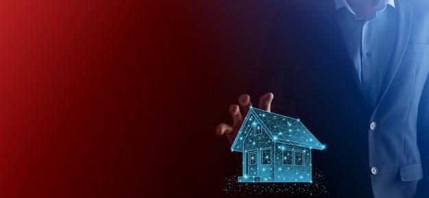 Człowiek posiada niski wielokąt. pojęcie nieruchomości, biznesmen posiadający ikonę domu. dom na rękę. pojęcie ubezpieczenia i bezpieczeństwa nieruchomości. ochronny gest człowieka i symbol domu