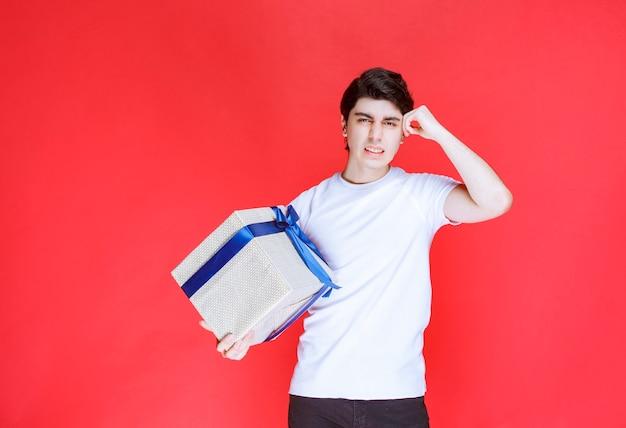 Człowiek posiadający białe niebieskie pudełko i myślenia
